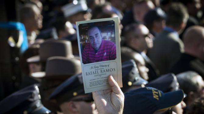 A man holds up a picture of slain New York City Police Officer Ramos near the Christ Tabernacle Church during his funeral service in New York