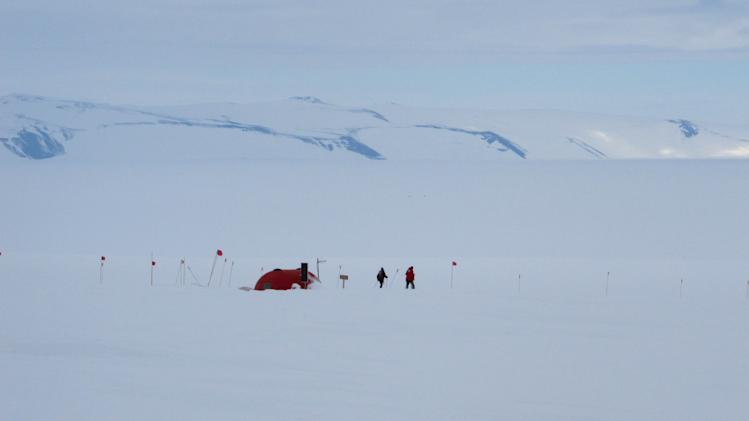 "In this Sunday, Jan. 20, 2013 photo, cross-country skiers pass a survival shelter on Hut Point Peninsula of Ross Island, Antarctica. Tourism is rebounding here five years after the financial crisis stifled what had been a burgeoning industry. And it's not just retirees watching penguins from the deck of a ship. Visitors are taking tours inland and even engaging in ""adventure tourism"" like skydiving and scuba diving under the ever-sunlit skies of a Southern Hemisphere summer. (AP Photo/Rod McGuirk)"