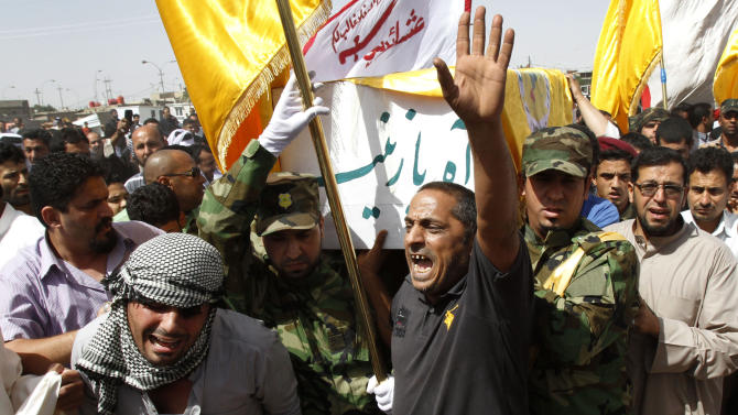 """Family members of Mohammed Aboud, chant slogans against the Sunni-dominated Free Syrian Army rebel group and the al-Qaida-affiliated Jabhat al-Nusra during his funeral in Basra, Iraq's second-largest city, 340 miles (550 kilometers) southeast of Baghdad, Iraq, Friday, May 17, 2013. Hundreds of Iraqis in Basra, have attended the funeral of two Shiite fighters killed in Syria. Relatives of Aboud say he was killed by a sniper fire near the shrine of Sayida Zeinab outside the capital of Damascus five days ago. Arabic writing on coffin reads, """"Sigh in grief, Zeinab."""" (AP Photo/ Nabil Al-Jurani)"""