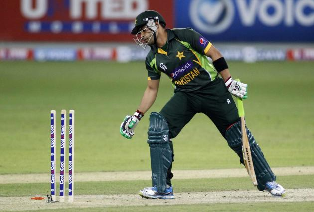 Pakistan's Akmal looks back after being bowled by Sri Lanka's Prasanna during their second Twenty20 international cricket match in Dubai