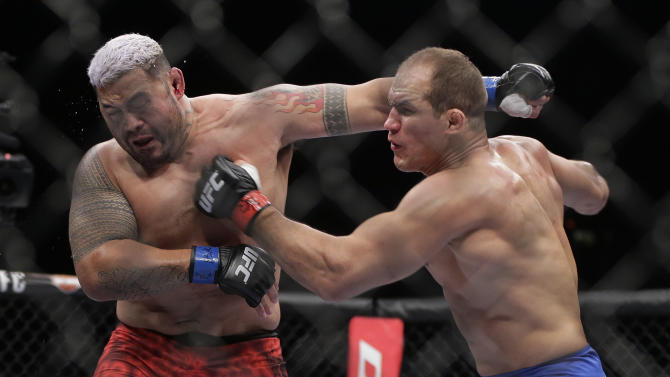 Mark Hunt, left, exchanges punches with Junior dos Santos during the second round of a UFC 160 mixed martial arts heavyweight bout, Saturday, May 25, 2013, in Las Vegas. Dos Santos won by knockout in the third round. (AP Photo/Julie Jacobson)