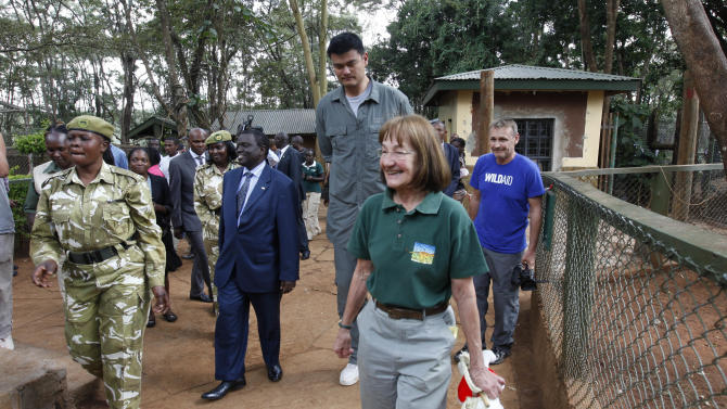 Yao Ming, China's top basketball star, middle, with KWS Staff, Thursday, Aug. 16, 2012, in Kenya National Park Orphanage in Nairobi, Kenya. Ming is visiting Kenya on his first-ever visit to Africa to film a documentary aimed at reducing poaching attacks against elephants and rhinos. The two animals are coming under increasing attacks by poachers who sell rhino horns and elephant tusks to buyers in Asia who acquire the animal products as a sign of affluence. Ming has spent nearly a week in Kenya, visiting wildlife parks where he has seen elephant carcasses killed by poachers. (AP Photo/Sayyid Azim)