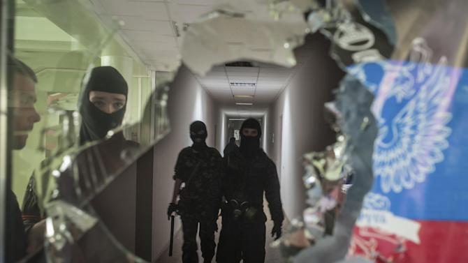 Masked pro-Russian militants patrol in the local administration building in Mariupol, Ukraine, Saturday, April 26, 2014. A pro-Russian insurgency leader in eastern Ukraine said Saturday that foreign military observers detained as suspected NATO spies could be released in exchange for jailed pro-Russian activists. (AP Photo/Evgeniy Maloletka)