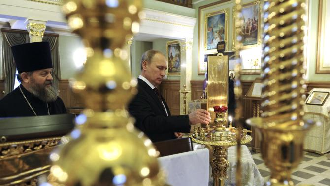 Russian President Vladimir Putin places a candle at a church as he visits the National Mineral Resources University in St. Petersburg