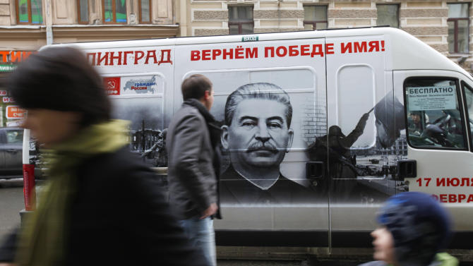 "People walk by a vehicle adorned with a portrait of Soviet dictator Josef Stalin and a sign reading ""Stalingrad gets back its victorious name""  in St. Petersburg, Russia, Saturday, Feb. 2, 2013. On Saturday Russia marked the 70th anniversary of the end of  the battle of Stalingrad. The city was renamed Volgograd in 1961, but the name Stalingrad is indelibly connected with the battle that is one of Russia's most-lauded military achievements. Stalin's image adorns five buses that are to run in Volograd until Russia observes Victory Day on May 9, and similar buses were to run Saturday in St. Petersburg and Chita. (AP Photo/Elena Ignatyeva)"