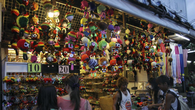 In this picture taken on Saturday, May 19,2012, tourists buy dolls at Chatuchak  Market in Bangkok, Thailand. Chaos is part of Bangkok's charm. But the savvy traveler quickly learns how to navigate Bangkok's legendary traffic jams and discover its soul, a mix of urban jungle and Buddhist serenity where shopping and eating are national pastimes. (AP Photo/