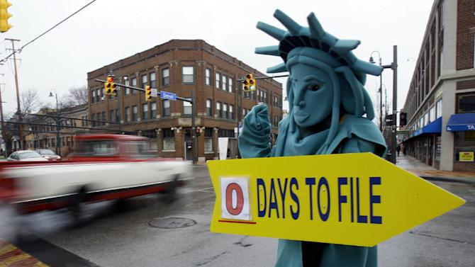 FILE-In this Monday, April 18, 2011, file photo, Max Martinez, dressed as the Statue of Liberty, tries to alert motorists on the final day to file taxes. A typical middle-income family making $40,000 to $64,000 a year could see its taxes go up by $2,000 in 2013 if lawmakers fail to renew a lengthy roster of tax cuts set to expire at the end of 2012, according to a new report Monday, Oct. 1, 2012. Taxpayers across the income spectrum would be hit with large tax hikes, the Tax Policy Center said in its study, with households in the top 1 percent income range seeing an average tax increase of more than $120,000, while a family making between $110,000 to $140,000 could see a tax hike in the $6,000 range. (AP Photo/Tony Dejak, File)