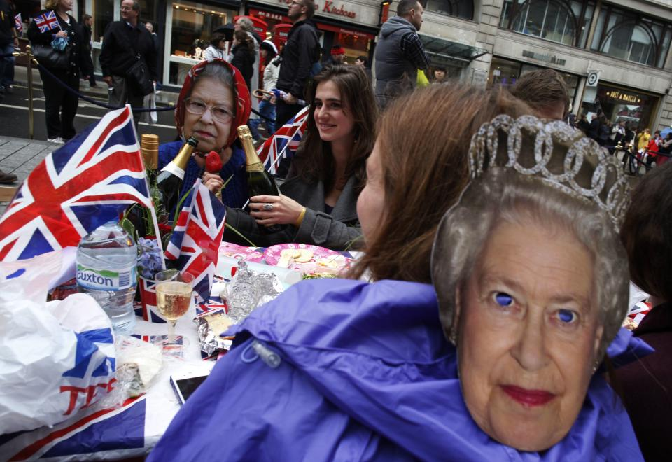 People wearing masks of Queen Elizabeth II share in the Big Jubilee Lunch  at the Piccadilly Jubilee street party, in London Sunday June 3, 2012 to mark Queen Elizabeth II's 60 years on the British throne.(AP Photo/Elizabeth Dalziel)