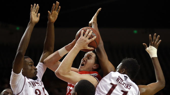 New Mexico forward Joe Furstinger, center, is fouled by New Mexico State forward Johnathon Wilkins, right, as Jalyn Pennie (35) watches during the first half of an NCAA college basketball game in Las Cruces, N.M., Saturday, Dec. 20, 2014. (AP Photo/Andres Leighton)