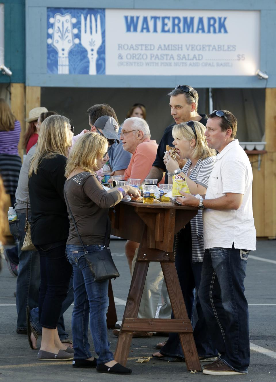 In this Sept, 28, 2013 photo, people dine standing up at outdoor tables at the Southern Ground Music & Food Festival in Nashville, Tenn. Musicians are encouraging the city's burgeoning food culture by turning the spotlight on local chefs and restaurants. (AP Photo/Mark Humphrey)