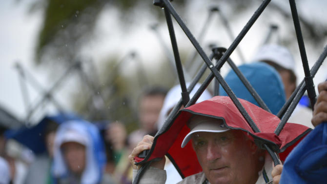 Spectators at the 18th hole use their chairs as cover as rain falls during the second round of the Arnold Palmer Invitational golf tournament in Orlando, Fla., Friday, March 22, 2013.(AP Photo/Phelan M. Ebenhack)