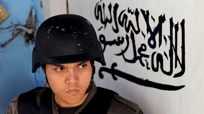 """An Indonesian police officer stands guard at the door of the house of a suspected terrorist after a raid in Jakarta, Indonesia, Saturday, Oct. 27, 2012. Indonesian police say they have arrested 11 people suspected of planning a range of terrorist attacks on domestic and foreign targets including the U.S. and Australian embassies. Arabic writing in the background reads """"There is no God but Allah and Muhammad is His messenger."""" (AP Photo/Jefta)"""