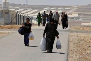 Newly-arrived Syrian refugees carry their belongings as they walk at Azraq refugee camp