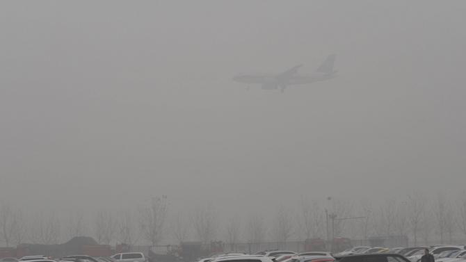 A plane descends to land at the Beijing Capital International Airport amid heavy smog
