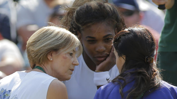 Court officials talk to Serena Williams of the U.S as she and Venus Williams retire after 3 games from their women's doubles match against Kristina Barrois of Germany and Stefanie Voegele of Switzerland at the All England Lawn Tennis Championships in Wimbledon, London, Tuesday July 1, 2014. (AP Photo/Pavel Golovkin)