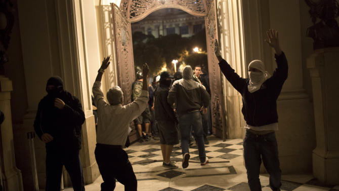 A worker, center left, tries to remove protesters after they invaded the city council building in Rio de Janeiro, Brazil, Wednesday, July 31, 2013. The clash came toward the end of an anti-government march Wednesday by protesters who focused their anger on Rio state governor Sergio Cabral. Nationwide anti-government protests started in Brazil in June. Complaints target poor public services in the face of citizen's heavy tax burden. (AP Photo/Felipe Dana)