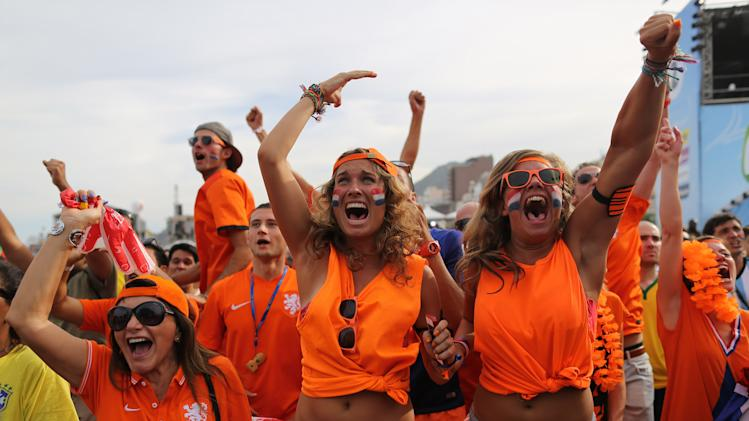 Soccer fans, decked out in orange, the Netherlands' national color, celebrate their side's second goal scored by Memphis Depay, while watching a live broadcast of the group B World Cup match between Chile and Netherlands, inside the FIFA Fan Fest area on Copacabana beach, in Rio de Janeiro, Brazil, Monday, June 23, 2014. Netherlands won 2-0, taking the top spot in group B. (AP Photo/Leo Correa)