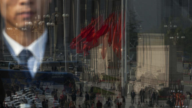 Journalists, firemen, buses, and red flags on Tiananmen are reflected in a glass door of the Great Hall of the People, where opening ceremony of the 18th Communist Party Congress is held, while a soldier dressed as an usher, seen through the glass, keeps watching in Beijing, Thursday, Nov. 8, 2012. China's ruling Communist Party opened a congress Thursday to usher in a new group of younger leaders faced with the challenging tasks of righting a flagging economy and meeting public calls for better government. (AP Photo/Alexander F. Yuan)