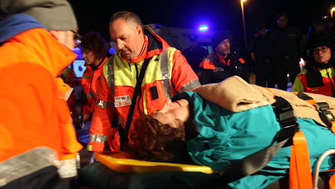 A woman is carried by paramedics as passengers of the ferry that caught fire in the channel between Italy and Albania are transported to the town of Otranto, near Lecce, southern Italy, Sunday, Dec. 28, 2014. Italian and Greek rescue crews battled gale-force winds and massive waves as they struggled Sunday to evacuate hundreds of people from a ferry on fire and adrift in the channel between Italy and Albania. At least one person died and two were injured. The fire broke out before dawn Sunday on a car deck of the Italian-flagged Norman Atlantic, traveling from the western Greek port of Patras to the Italian port of Ancona on the Adriatic, with 422 passengers and 56 crew members on board. (AP Photo/Ivan Tortorella)