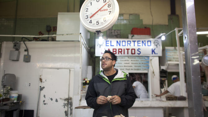 In this July 27, 2012 photo, U.S. Chef Christopher Kostow talks to a vendor as he shops at a food market in Mexico City. Kostow, whose Restaurant at Meadowood in Napa Valley has three Michelin stars, wanted to sample the diversity of the country's fresh ingredients. (AP Photo/Alexandre Meneghini)