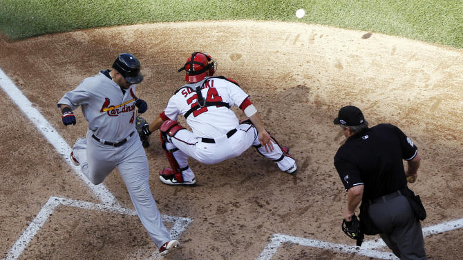 St. Louis Cardinals' Yadier Molina, left, scores a run in front of Washington Nationals catcher Kurt Suzuki on a sacrifice fly by Daniel Descalso in the sixth inning of Game 3 of the National League division baseball series against the Washington Nationals on Wednesday, Oct. 10, 2012, in Washington. Home plate umpire Joe West, right, watches the play. (AP Photo/Alex Brandon)