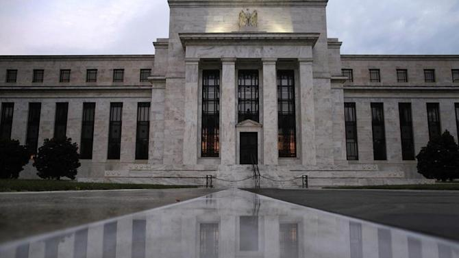 The facade of the U.S. Federal Reserve building is reflected on wet marble during the early morning hours in Washington