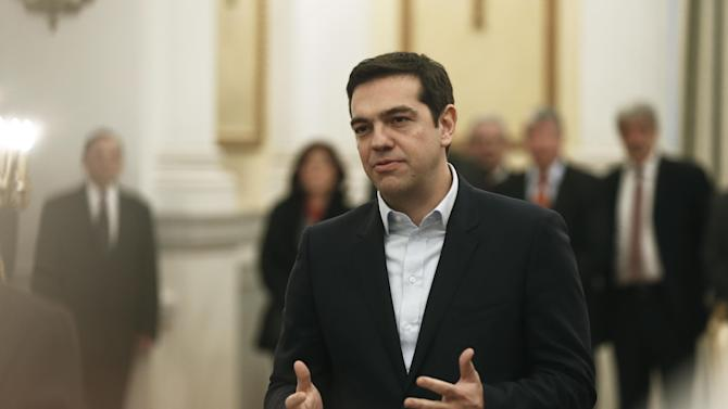 Greece's Prime Minister Alexis Tsipras, makes a secular oath to the Greek President Karolos Papoulias at the Presidential Palace in Athens, Monday, Jan. 26, 2015. Radical left leader Alexis Tsipras has been sworn in as Greece's new prime minister, becoming the youngest man to hold the post in 150 years. The 40-year-old broke with tradition and took a secular oath rather than the Greek Orthodox religious ceremony with which prime ministers are usually sworn in.(AP Photo/Petros Giannakouris)