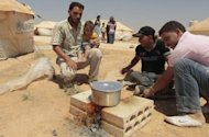 Syrian refugees cook at the Zaatari refugee camp in the Jordanian city of Mafraq, near the border with Syria, on August 6. A charity that cares for thousands of Syrians who fled violence said last week that the first official camp to house the refugees in neighbouring Jordan falls short of international standards