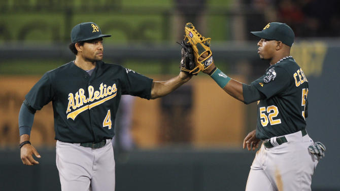 Oakland Athletics center fielder Coco Crisp, left, and center fielder Yoenis Cespedes celebrates their 5-3 win against the Los Angeles Angels during a baseball game in Anaheim, Calif., Tuesday, April 17, 2012. (AP Photo/Chris Carlson)