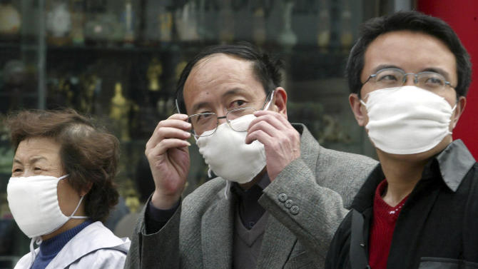 FILE - In this Monday, April 21, 2003 file photo, a Chinese man wearing a mask removes his glasses while walking with others in downtown Beijing, China. A genetic variant commonly found in Chinese people may help explain why some patients got seriously ill with swine flu, a discovery scientists say could help pinpoint why flu viruses hit some populations particularly hard and change how they're treated. Less than one percent of Caucasians are thought to have the gene alteration, which has previously been linked to severe influenza. About 25 percent of Chinese have the gene variant, which is also common in Japanese and Korean people. (AP Photo/Ng Han Guan, File)