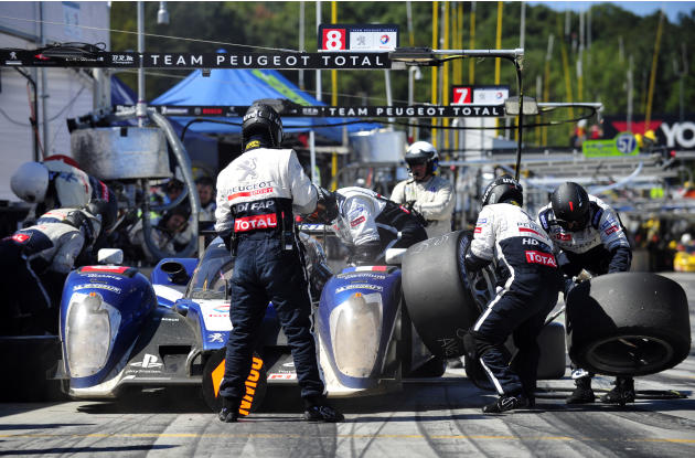 The Peugeot crew works on the car of Stephane Sarrazin, of France, during a pit stop in the American Le Mans Series' Petit Le Mans auto race at Road Atlanta, Saturday, Oct. 1, 2011, in Braselton, Ga.