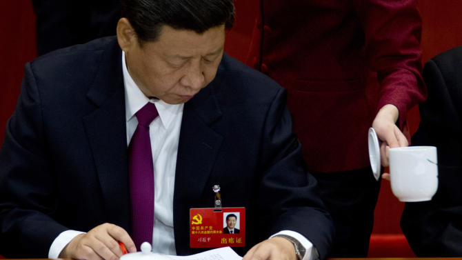An attendant serves tea while Chinese Vice President Xi Jinping attends the opening session of 18th Communist Party Congress at the Great Hall of the People in Beijing, China, Thursday, Nov. 8, 2012. Preparing to hand over power after a decade in office, China's President Hu Jintao called Thursday for sterner measures to combat official corruption that has stoked public anger while urging the Communist Party to maintain firm political control. (AP Photo/Alexander F. Yuan)