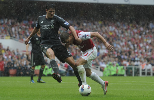 Arsenal's Andrey Arshavin, right,  grapples with Liverpool's Martin Kelly during their English Premier League soccer match at the Emirates stadium, London, Saturday, Aug. 20, 2011. (AP Photo/Tom Hevezi)