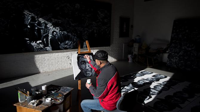 In this photo taken on Tuesday, Dec. 25, 2012, Beijing-based artist Liu Yi paints a portrait of a Tibetan who have self-immolated over the past three years, at his studio in Songzhuang art village in Tongzhou, on the outskirt of Beijing. Liu is working on a series of black-and-white portraits he knows will never be shown in a Chinese gallery. His varied subjects - men and women, young and old, smiling and pensive - have one thing in common: They are Tibetans who have set themselves on fire to protest repressive Chinese rule. (AP Photo/Andy Wong)