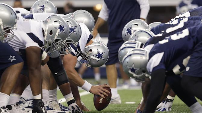 In this Thursday, June 19, 2014, file photo, the Dallas Cowboys field goal unit lines up for drill during NFL football minicamp at the team's stadium in Arlington, Texas. A players' union lawsuit accusing NFL team owners of setting a secret salary cap in 2010 was kept alive by a federal appeals court Friday, June 20, 2014. The three-judge appeals court panel that heard oral arguments in January disagreed with U.S. District Judge David Doty on one of the NFLPA's two arguments for pursuing damages despite the 2011 collective bargaining agreement that was supposed to settle such lawsuits. The appeals court sent the case back to Doty's jurisdiction in Minneapolis for further proceedings