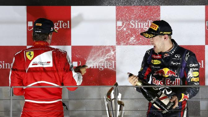Ferrari Formula One driver Alonso and Red Bull Formula One driver Vettel celebrate with champagne on the podium after the Singapore F1 Grand Prix in Singapore