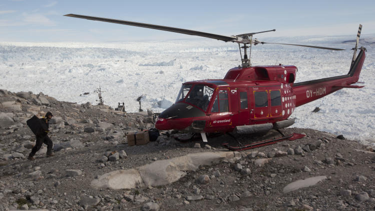 In this July 19, 2011 photo, with the Jakobshavn ice fjord visible in the background, a researcher loads gear onto a helicopter retrieving him and his team from a site near the edge of the Greenland Ice Sheet, outside Ilulissat, Greenland. Across Greenland's vast white landscape, teams of researchers from around the world are searching for clues to the potential effects of global warming on Greenland's ice. (AP Photo/Brennan Linsley)