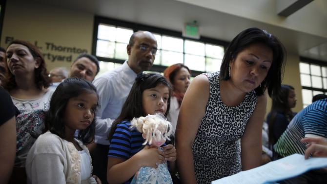 Adiba Tahsin Rysa, from Bangladesh, and Daniela Negrete, from Mexico, check in before a U.S. citizenship ceremony for 80 immigrant children and youths in Los Angeles
