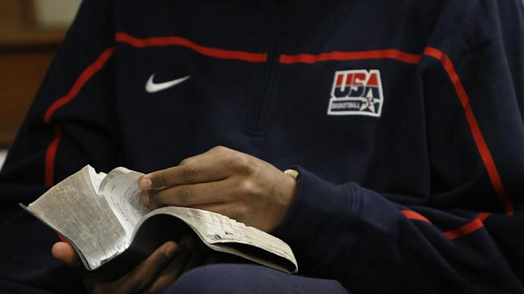 """In this photo taken in Chicago, on Monday, March 12, 2012, high school basketball phenom Jabari Parker  looks up scripture during a youth Bible study at the  Church of Jesus Christ of Latter-day Saints seminary in Chicago's Hyde Park neighborhood. Parker, chooses to wake up around 5 a.m. three times a week before school and head to the Bible study.  """"It gives me a better view of life,"""" he says. (AP Photo/Charles Rex Arbogast)"""