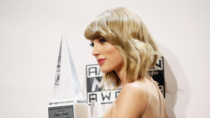 Taylor Swift poses with her award during the 42nd American Music Awards in Los Angeles