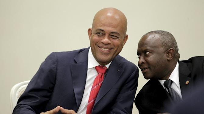 Haiti's president Michel Martelly speaks with Representatives Chamber president Cholcer Chanzy during an agreement signing at the National Palace in Port-au-Prince, Haiti