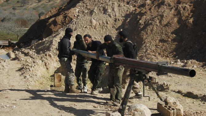 Rebel fighters prepare a Grad rocket to be launched toward forces of Syria's President Assad stationed in al-Suqaylabiyah district, from the orchards north of Kfar Zeita village in the northern countryside of Hama