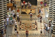 Visitors admire on September 2, 2012 the mosaic floor in the Siena cathedral