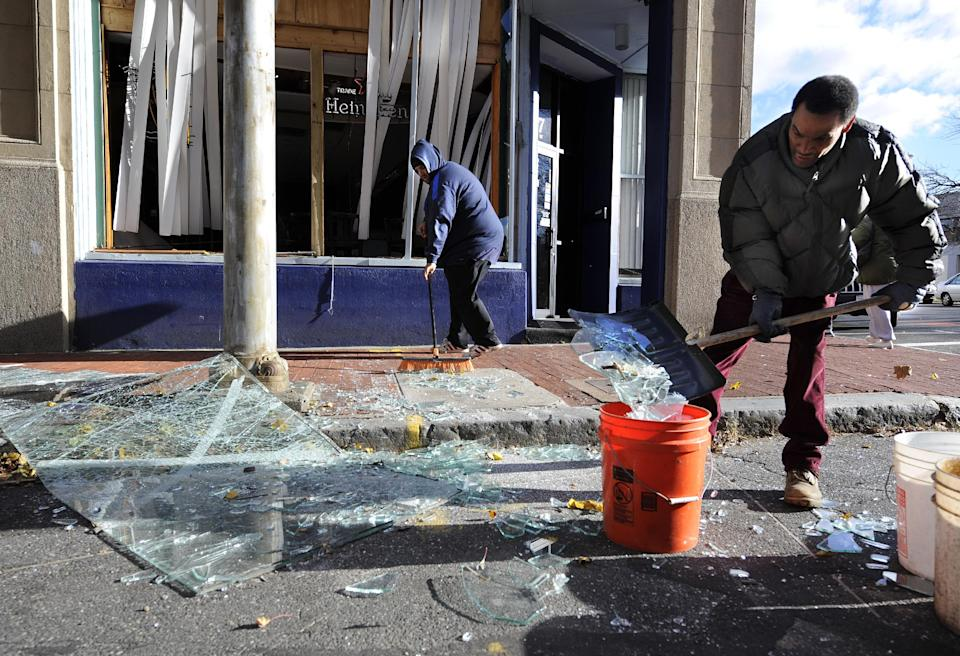Robert Spano, left, and Alan Hugley clean up broken glass, Saturday, Nov. 24, 2012, outside of Punta cana Restaurant & Bar, a few blocks from the site of a Friday-evening gas explosion that leveled a strip club in Springfield, Mass. (AP Photo/Jessica Hill)