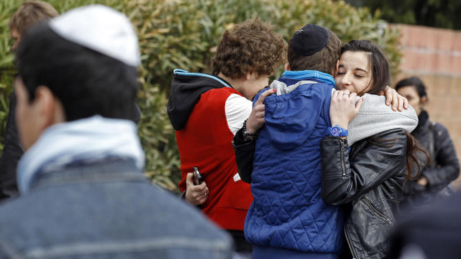 Students comfort each other at the Ozar Hatorah Jewish school where a gunman opened fire killing four people in Toulouse, southwestern France, Monday, March 19, 2012. A father and his two sons were among four people who died Monday when a gunman opened fire in front of a Jewish school in a city in southwest France, the Toulouse prosecutor said Monday. (AP Photo/Remy de la Mauviniere)