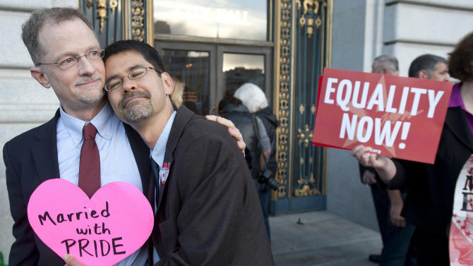 John Lewis, left, and Stuart Gaffney embrace outside San Francisco's City Hall shortly before the U.S. Supreme Court ruling cleared the way for same-sex marriage in California on Wednesday, June 26, 2013. The justices issued two 5-4 rulings in their final session of the term. One decision wiped away part of a federal anti-gay marriage law that has kept legally married same-sex couples from receiving tax, health and pension benefits. The other was a technical legal ruling that said nothing at all about same-sex marriage, but left in place a trial court's declaration that California's Proposition 8 is unconstitutional. (AP Photo/Noah Berger)