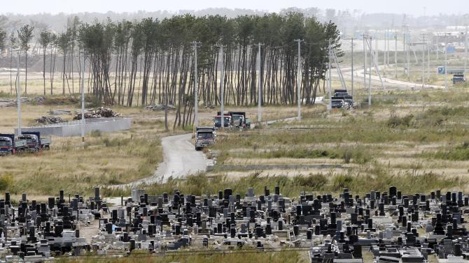 In this Oct. 10, 2012 photo, grave stones stand in a cemetery near pine trees, part of breakwater forest, that survived the March 11, 2011 earthquake and tsunami, near the Arahama beach in Sendai, northeastern Japan. Japan's accounting of its budget for reconstruction from the disasters is crammed with spending on unrelated projects, while all along Japan's northeastern coast, dozens of communities remain uncertain of whether, when and how they will rebuild. (AP Photo/Koji Sasahara)