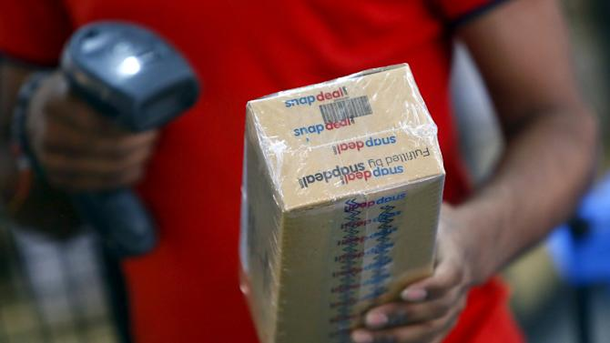A worker of  Indian e-commerce company Snapdeal.com scans barcode on a box after it was packed at the company's warehouse in New Delhi