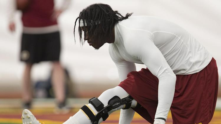 Washington Redskins' quarterback Robert Griffin III warms up during a NFL football minicamp at Redskins Park, Tuesday, June 11, 2013, in Ashburn, Va.. (AP Photo/Carolyn Kaster)