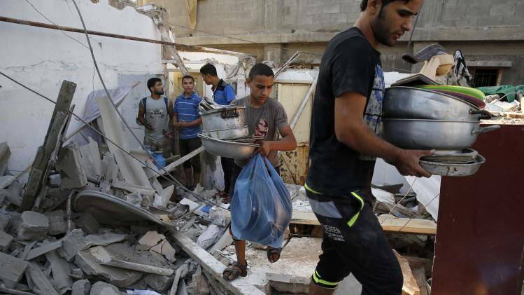 Palestinians salvage belongings from a destroyed home in Gaza City